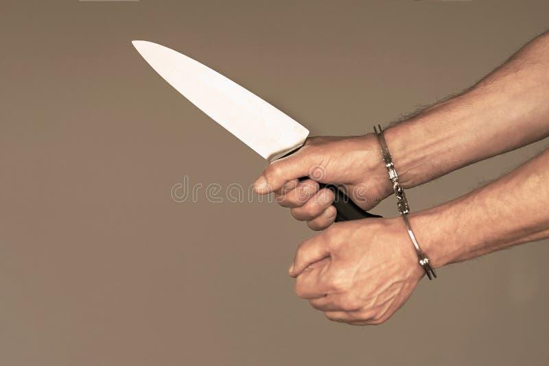 Kriminelle Hände sperrten in Handschellen Mann, der ein Messer hält Weiche Farben stockfotografie