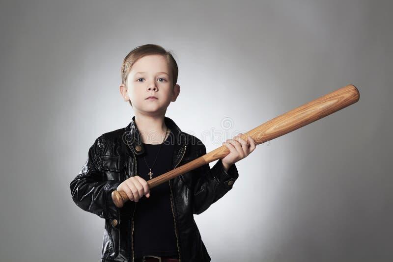 Krimineller Junge mit Baseballschläger Lustiges Kind im Ledermantel stockfoto