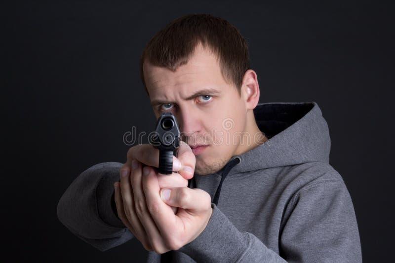 Kriminelles Zielen des Mannes mit Gewehr über Grau stockfotografie