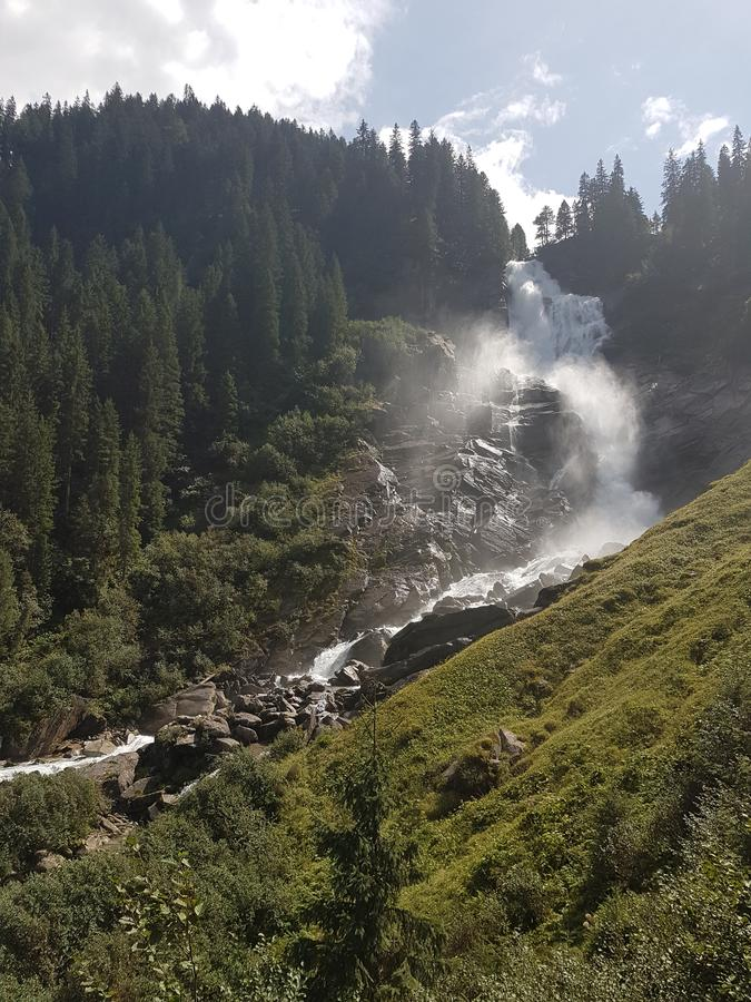 Krimml siklawy Austria gnania woda z krańcową władzą otaczającą wysokimi zielonymi drzewami i błękitnym jaskrawym niebem fotografia royalty free
