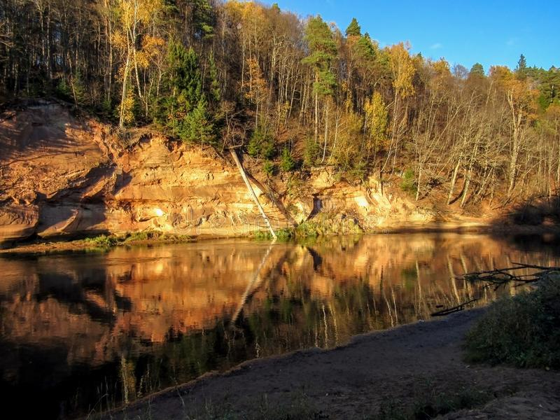 Autumn landscape of Devils Cave Rocks outcrop geological feature and yellow trees reflecting in Gauja river, Latvia stock image