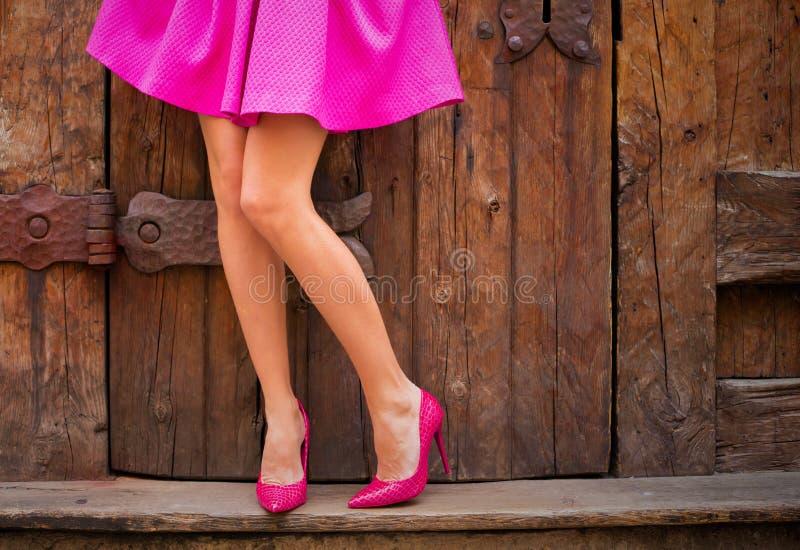 Kringgår bärande rosa färger för kvinna och skor för hög häl royaltyfri fotografi