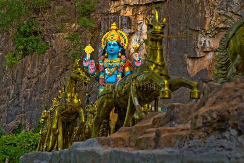 Krishna Hindu gudstaty med guld- hästar i Batu grottor Gombak royaltyfri fotografi