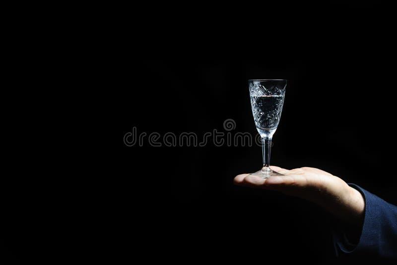 Kristalglas met wodka op een zwarte achtergrond stock afbeelding