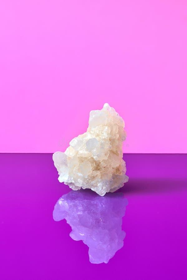 Kristall des Seesalzes mit reflaction isolatad auf einem duotone Veilchenhintergrund stockfotos