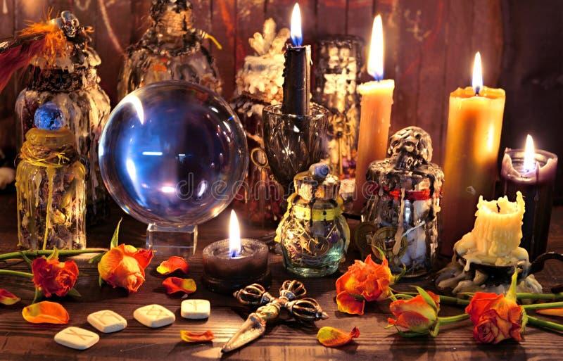 Kristallen bol met runen, zwarte kaars en heksen magische fles stock fotografie