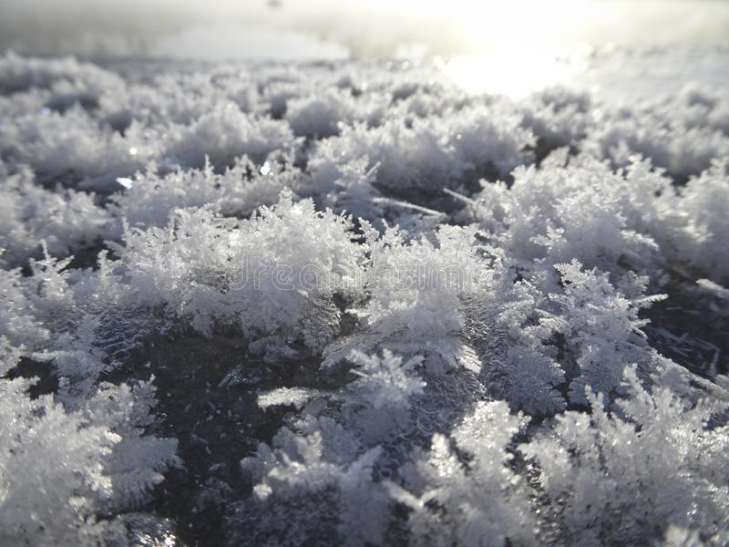 Kristallen van sneeuwvlokken op het ijs tegen een bevroren rivier stock afbeeldingen
