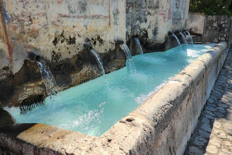 Kristallene Wasserstrahlen vom alten setzen Brunnen in Alcara Li Fusi herab lizenzfreie stockbilder