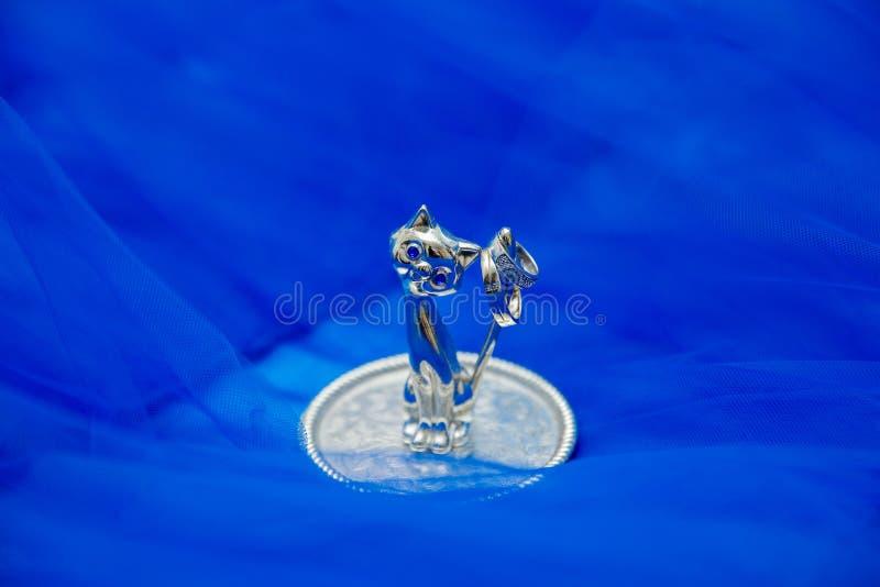 Kristallfigürchenkatze mit Ringen auf einer Platte an stockbilder