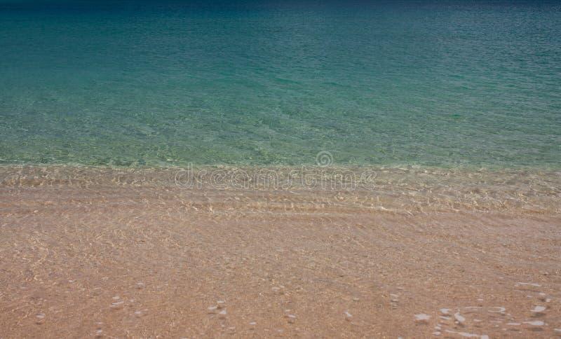 Kristallklart hav för halva och halvasand på den tropiska Tonga arkivfoto