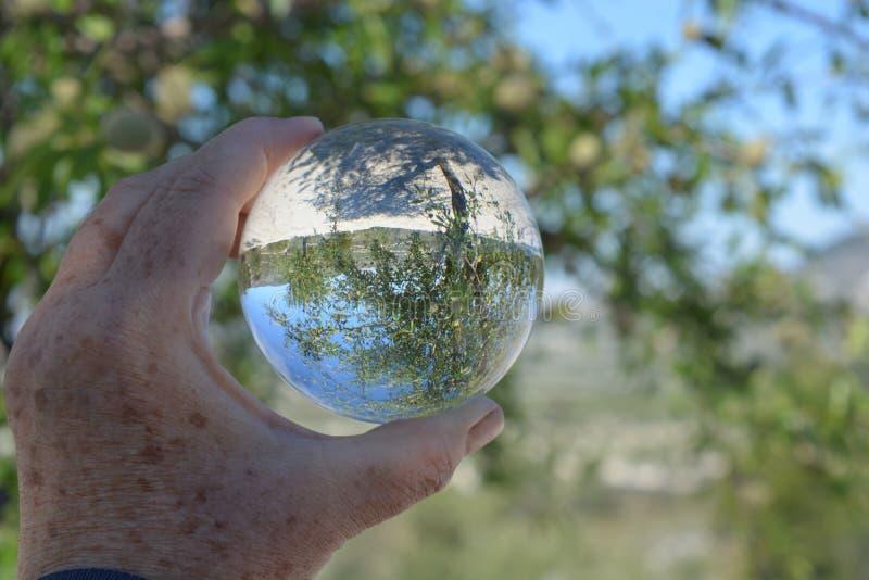 Kristallkula i handen, id?rikt refraktionfotografi royaltyfri fotografi