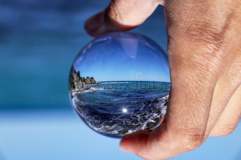 Kristallkula med recletion av Aphroditebadstranden på morgonljus Bollinnehav för exponeringsglas/Lens i hand med det blåa klara h arkivbilder