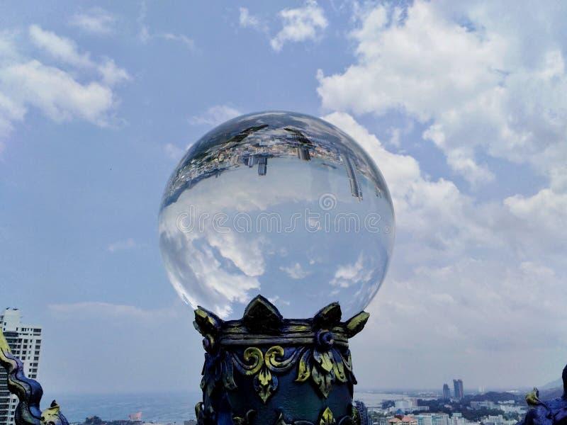 Kristallkula som reflekterar stadshimlen, härliga moln royaltyfri fotografi