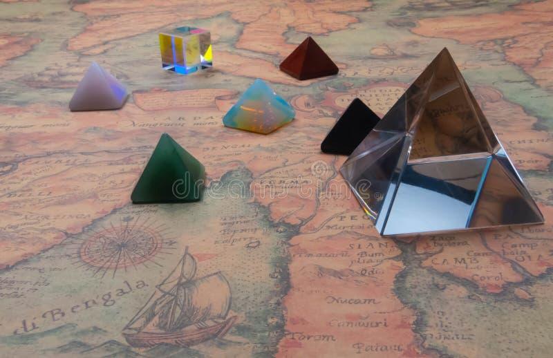 Kristallpyramide och små pyramider av naturliga gemstones med den ljusa kuben på en forntida världskarta arkivbild
