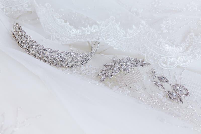 Kristallschmuck: Ohrringe, Haarnadel, Diadem auf einem weißen Heiratshintergrund lizenzfreie stockfotografie