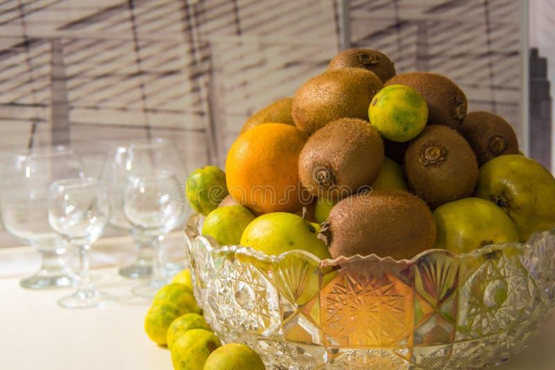 Kristallvase mit Früchten: Kiwi, Kalk, Orange, Apfel stockfotos