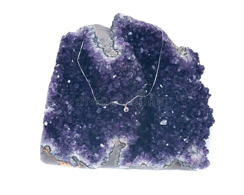 Kristaltegenhanger op zilveren die ketting op violetkleurige geode wordt voorgesteld stock foto