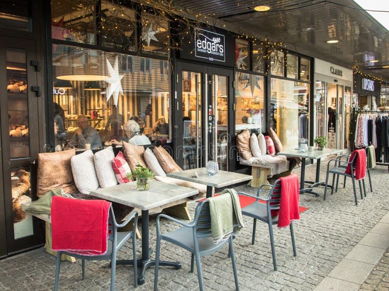 Kristansand, Norvegia, il 22 dicembre 2017: Sedie e tavole all'aperto a Edgars Bakeri, un forno nella città di Kristiansand immagine stock libera da diritti