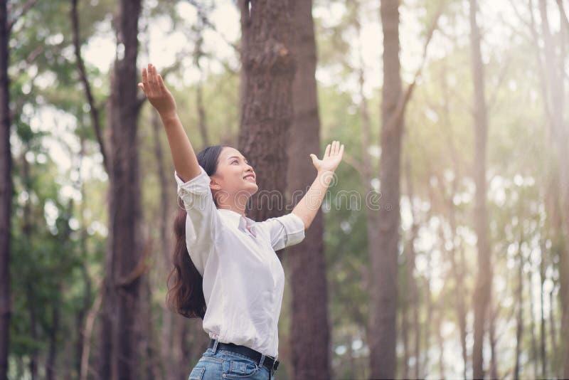 Kristen dyrkan med den lyftta handen i pinjeskogen, lycklig kvinna de royaltyfri bild