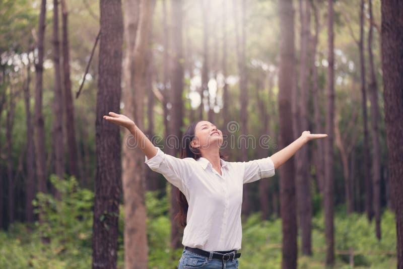 Kristen dyrkan med den lyftta handen i pinjeskogen, lycklig kvinna de arkivbilder
