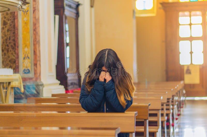 Kristen kvinna som ber i katolsk kyrka royaltyfria foton