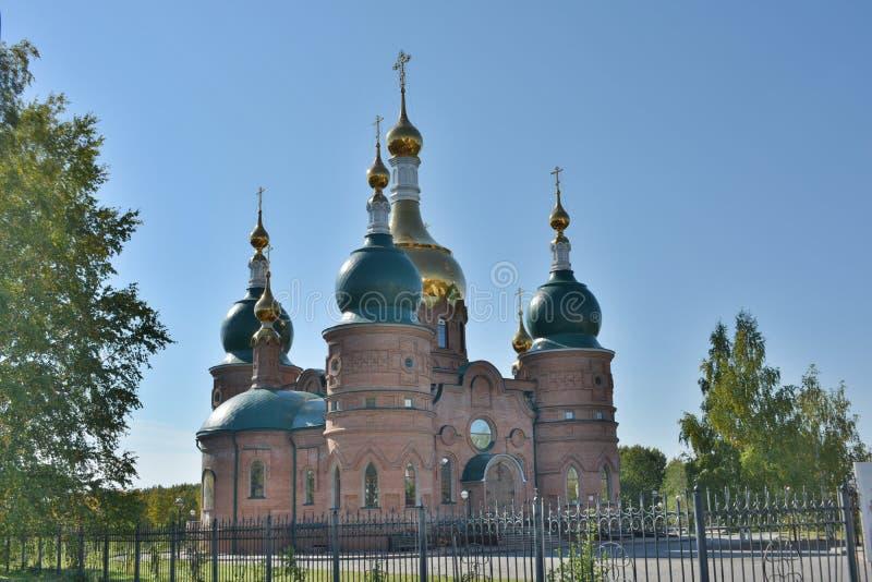 Kristen kyrka med gräsplan och guld- frilufts- kupoler arkivbilder