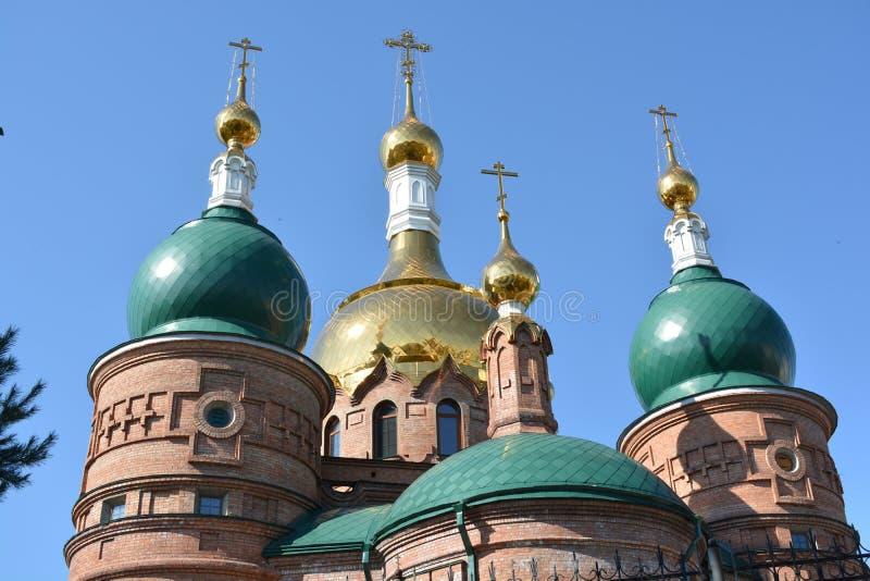 Kristen kyrka med gräsplan och guld- frilufts- kupoler royaltyfri foto