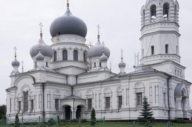Kristen ortodox vit kyrka med silver och gråa kupoler med guld- kors Lugna grå himmel över royaltyfria foton