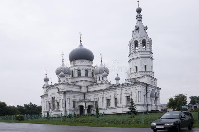 Kristen ortodox vit kyrka med silver och gråa kupoler med guld- kors Lugna grå himmel över arkivbild