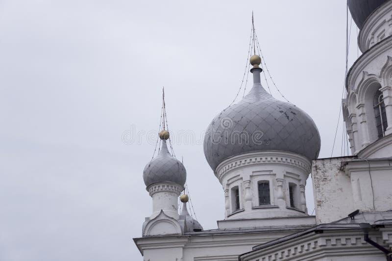 Kristen ortodox vit kyrka med silver och gråa kupoler med guld- kors Lugna grå himmel över arkivfoto