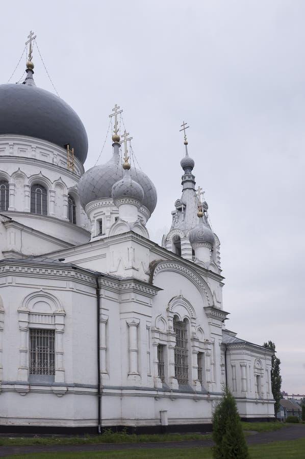 Kristen ortodox vit kyrka med silver och gråa kupoler med guld- kors Lugna grå himmel över fotografering för bildbyråer