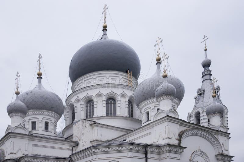 Kristen ortodox vit kyrka med silver och gråa kupoler med guld- kors Lugna grå himmel över royaltyfri foto