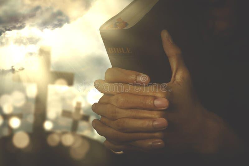 Kristen person som ber med bibeln royaltyfri foto
