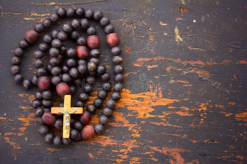 Kristen radbandbön med ett kors på gammal svart träbakgrund arkivbild