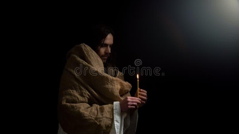 Kristen rymmande stearinljus i mörker, Jesus som ber för anda av folk, påsk royaltyfria foton