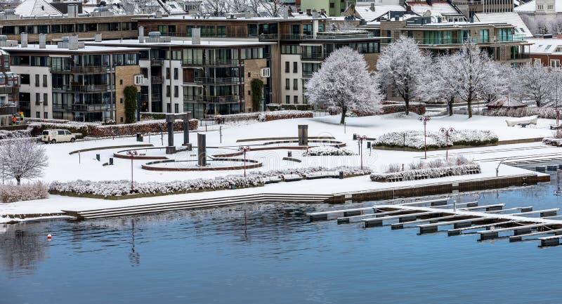 Kristiansand, Noruega - 17 de enero de 2018: El parque de Otterdals cubierto en nieve La fuente de agua en el puerto de fotografía de archivo