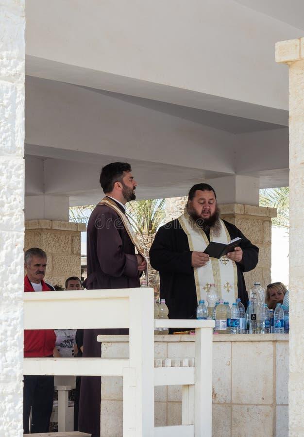 Kristna präster ber i närvaron av troenden på den turist- platsen Qasr el Yahud i Israel royaltyfria bilder