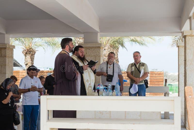 Kristna präster ber i närvaron av troenden på den turist- platsen Qasr el Yahud i Israel royaltyfria foton