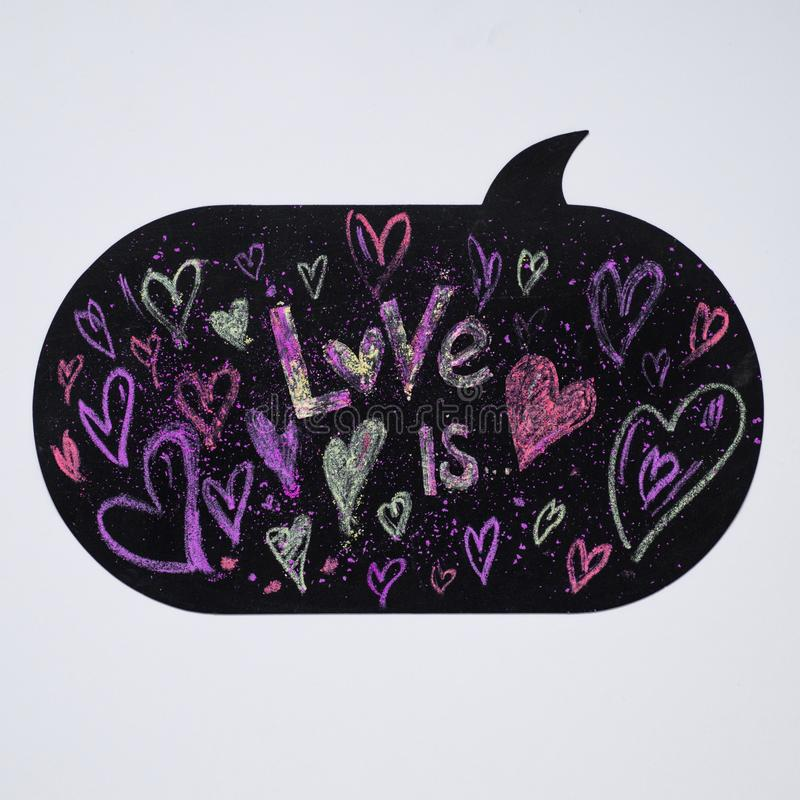 Krita drog hjärtor Bakgrund med textFÖRÄLSKELSE ÄR hjärta för gåvan för dagen för begreppet för den blåa asken för bakgrund isole arkivfoto