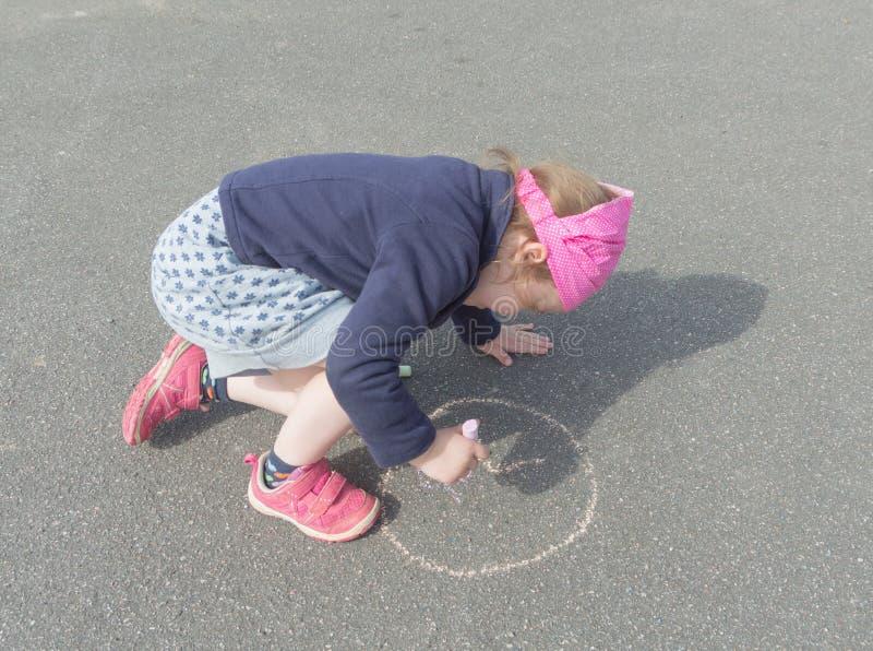 Krita på asfaltattraktion en cirkel behandla som ett barn flickan royaltyfri foto