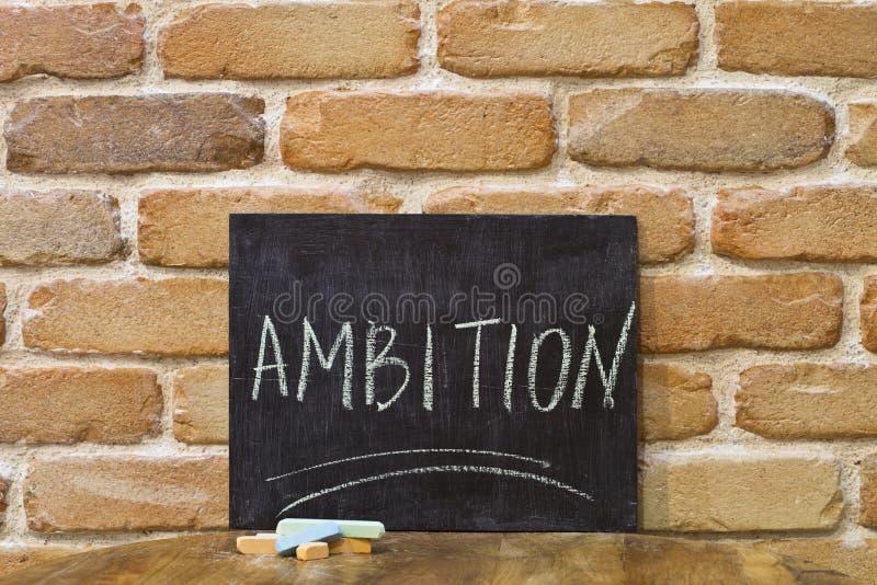 Kritabräde med ordet AMBITION att drunkna vid handen och chalks på trätabellen på bakgrund för tegelstenvägg royaltyfria bilder