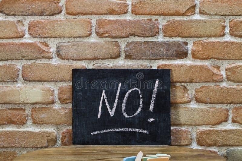 Kritabräde med ordet INTE! drunkna vid handen och chalks på trätabellen på bakgrund för tegelstenvägg arkivbild