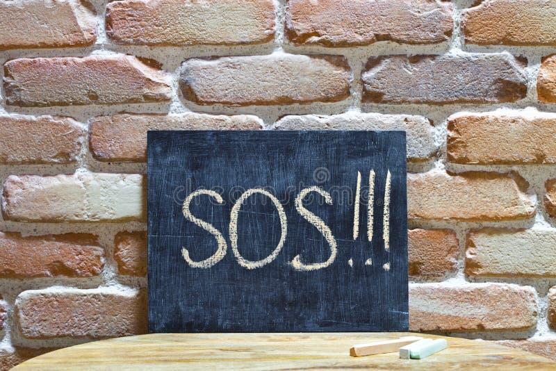 Kritabr?de med ordet SOS! drunkna vid handen och chalks p? tr?tabellen p? bakgrund f?r tegelstenv?gg royaltyfri fotografi