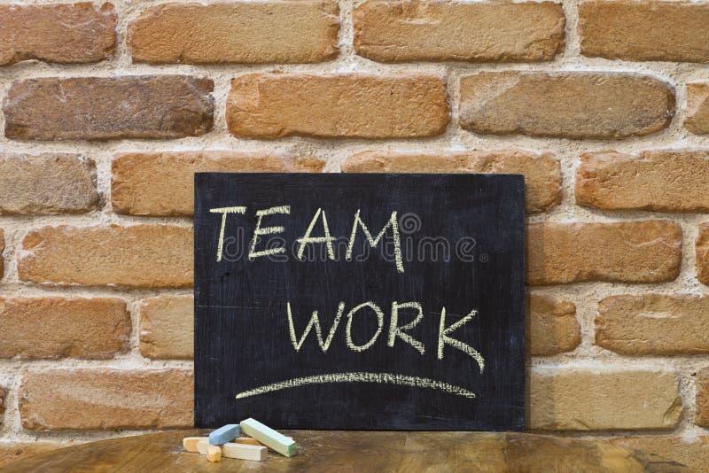 Kritabräde med ordet TEAMWORK att drunkna vid handen och chalks på trätabellen på bakgrund för tegelstenvägg arkivfoton
