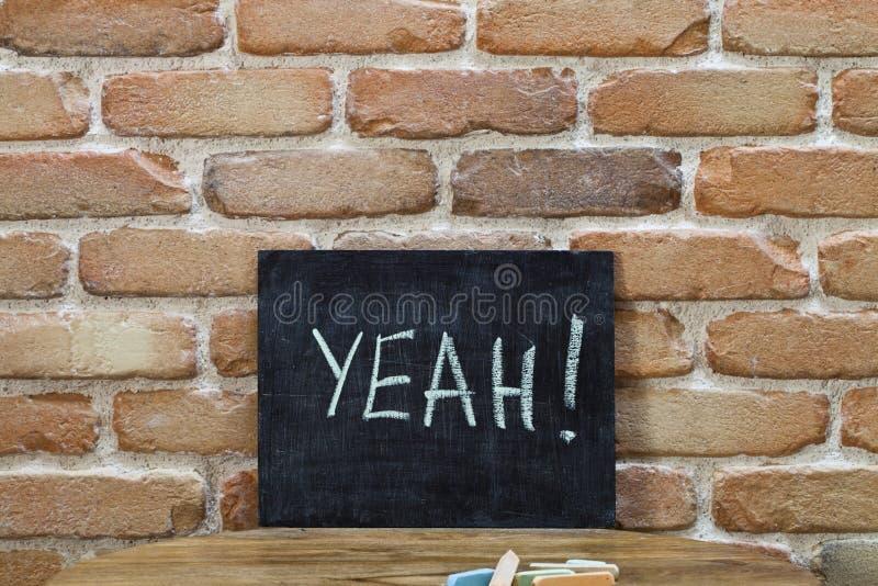 Kritabräde med ordet YEAH! drunkna vid handen och chalks på trätabellen på bakgrund för tegelstenvägg royaltyfria bilder