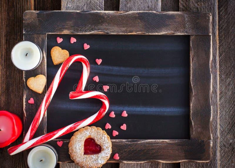 Kritabrädet och hjärta formade godisar och kakor royaltyfria foton