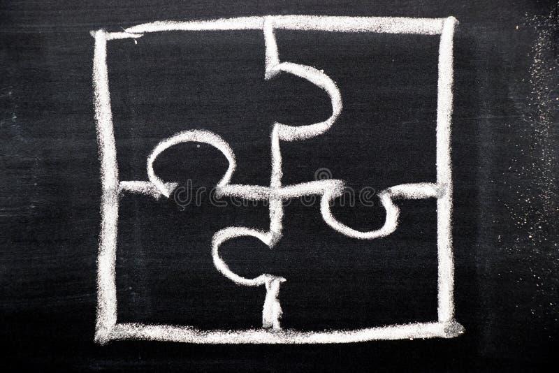 Kritahandteckning som pusselform på svart bräde royaltyfri foto