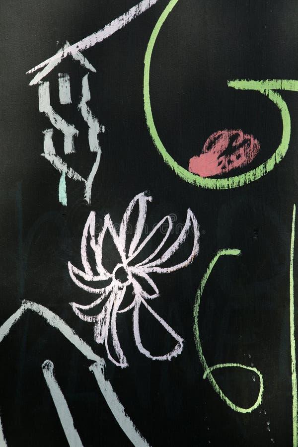 Kritateckning på svart tavlabakgrund arkivbild