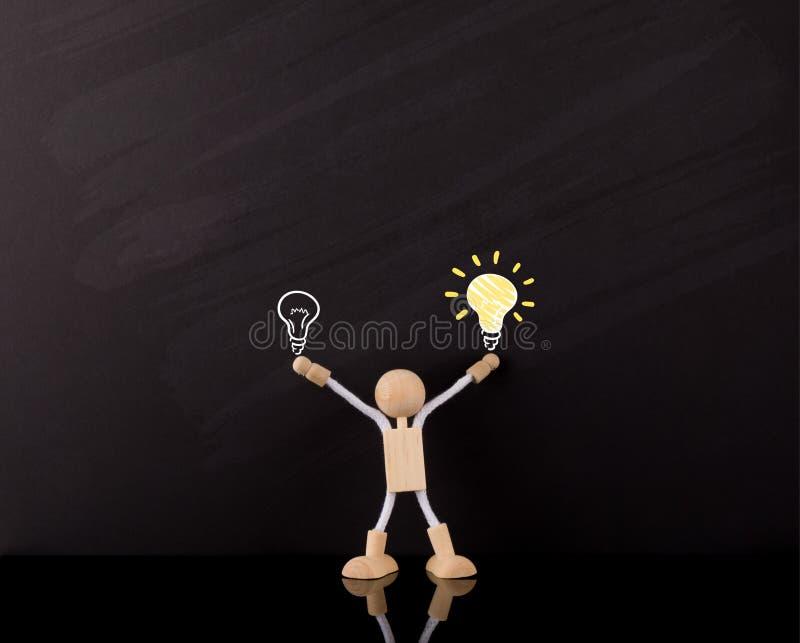 Kritisches denkendes Fähigkeits-Konzept, hölzerne Stock-Zahl Arme oben, große gelbe Glühlampeskizze, auf einer Tafel lizenzfreie stockfotos