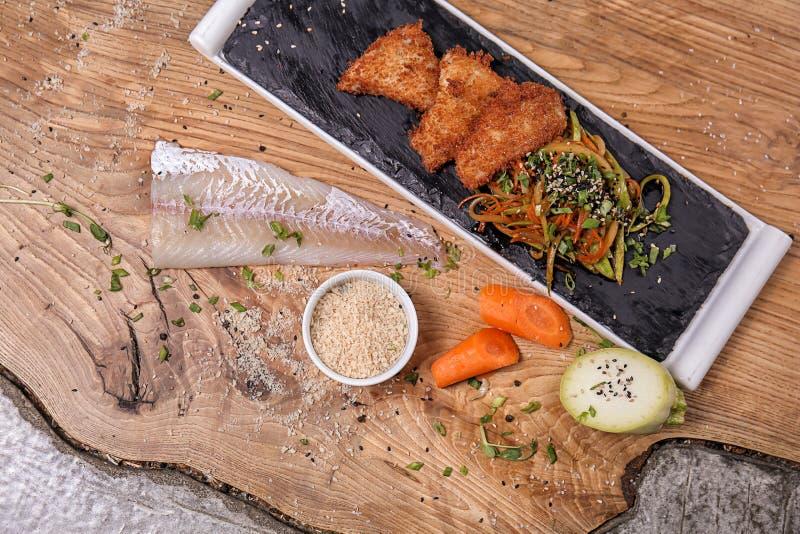 Kritisera plattan med stycken av stekt fisk och sallad på trätabellen royaltyfria bilder